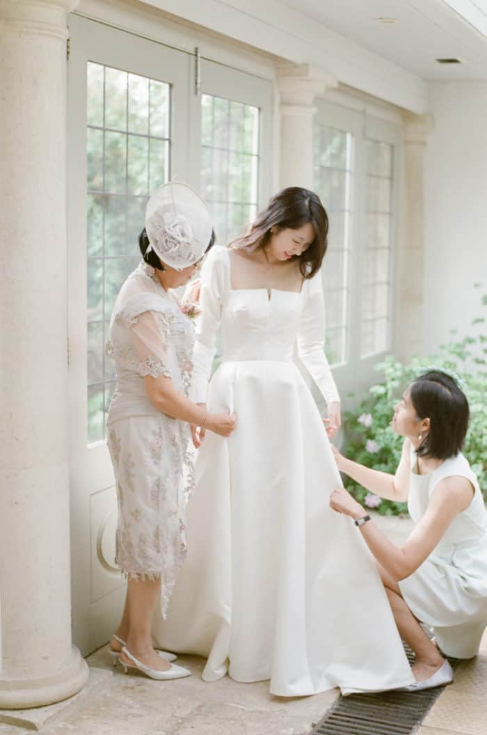Bride Getting Ready With Her Sister and Her Mom On Her Wedding Day At Barnsley House In The Cotswolds In England
