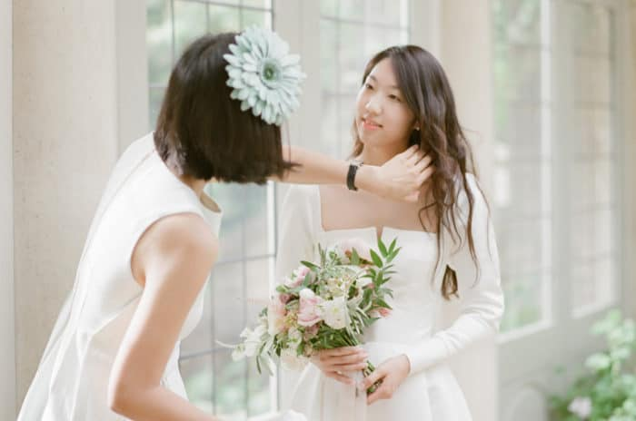 Bride Getting Ready With Her Sister On Her Wedding Day At Barnsley House In The Cotswolds In England