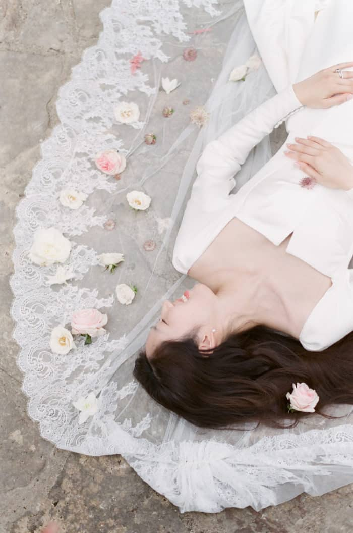 Bride Lying In Flower Bed On Her Wedding Day At Barnsley House In The Cotswolds In England