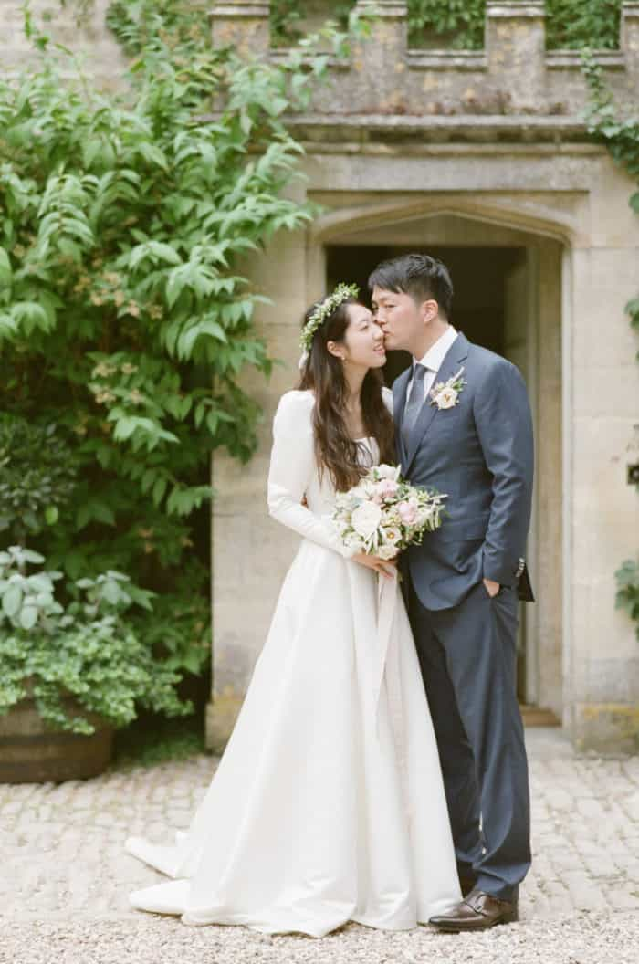 Kissing Couple On Their Wedding Day At Barnsley House In The Cotswolds In England