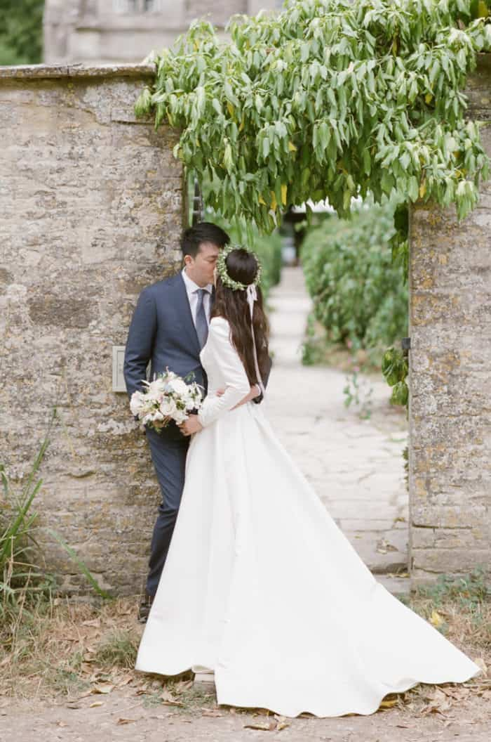 British Couple Kissing In Front Of Gate On Their Wedding Day At Barnsley House In The Cotswolds In England