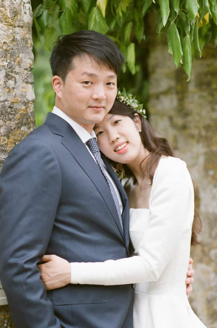 British Couple Hugging On Their Wedding Day At Barnsley House In The Cotswolds In England