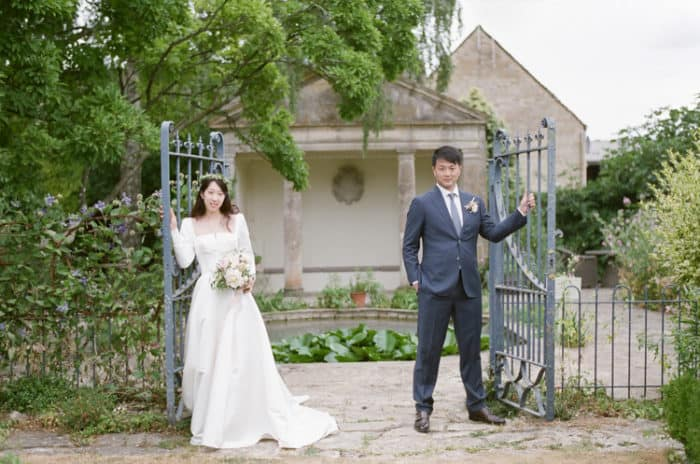 British Couple In The Gardens Of  The Barnsley House In The Cotswolds In England On Her Wedding Day
