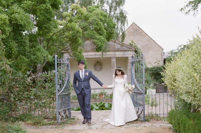 Happy British Couple Walking In The Gardens Of  The Barnsley House In The Cotswolds In England On Her Wedding Day