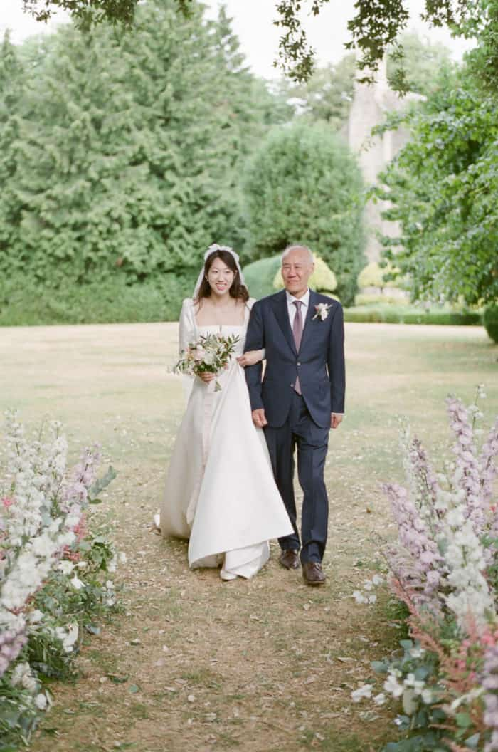 Dad Walking Bride Down The Aisle At Wedding Ceremony At The Barnsley House In The Cotswolds In England On Her Wedding Day