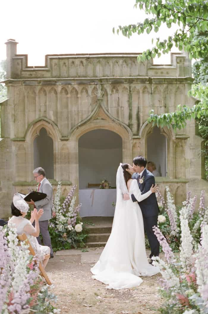 Wedding Couple Kissing During Their Wedding Ceremony At The Barnsley House In The Cotswolds In England On Her Wedding Day