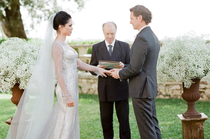 Bride And Groom Exchanging Rings During Their Ceremony At Borgo Pignano In Tuscany In Italy With Sposiamovi Events