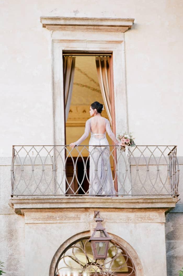 Bride On Balcony Of Borgo Pignano In Tuscany In Italy With Sposiamovi Events