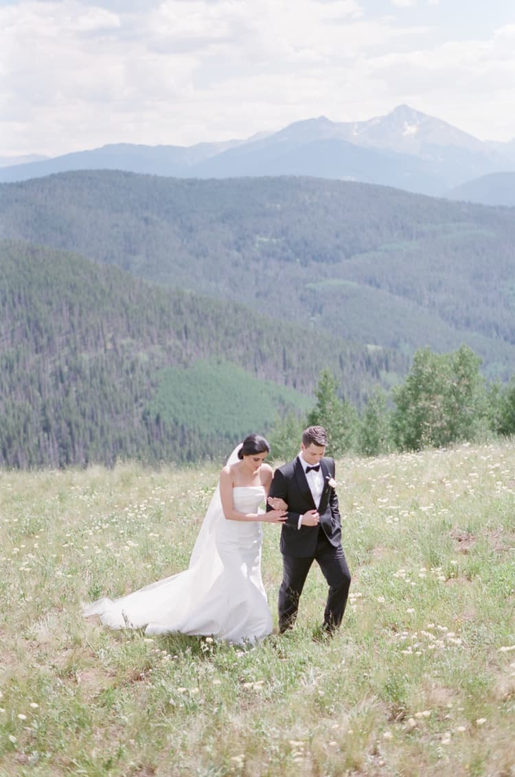 Bride And Groom Walking On Vail Mountain Top During Wedding Day In Summer With White Birch Weddings