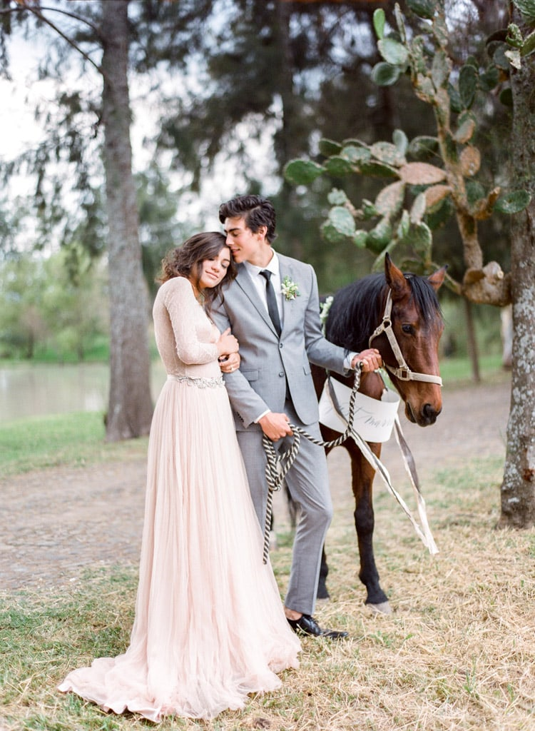 Bride & groom together with horse carrying a just married sign