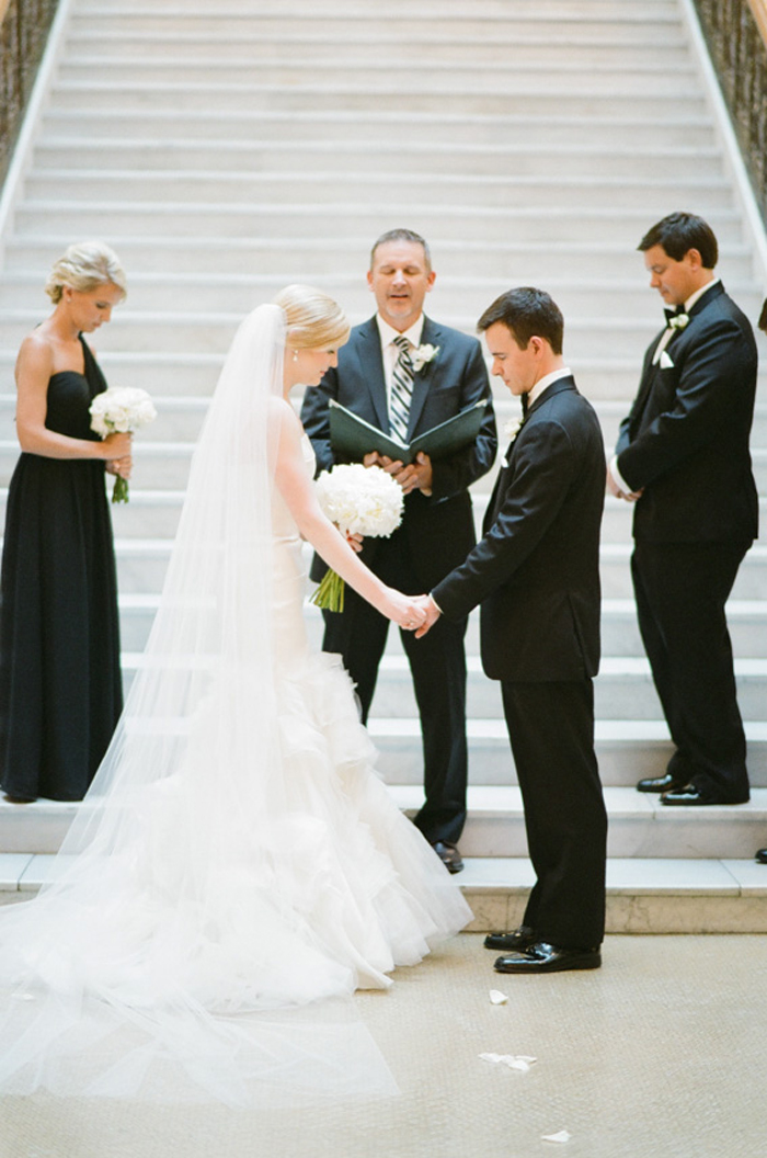Bride and groom hold hands in front of the grand staircase at The Rookery in Chicago