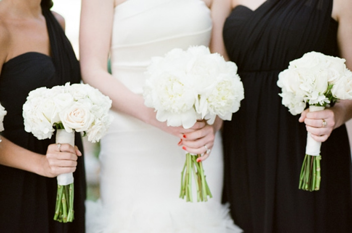 A bride and her bridesmaids hold classic white bouquets for a wedding at The Rookery in Chicago