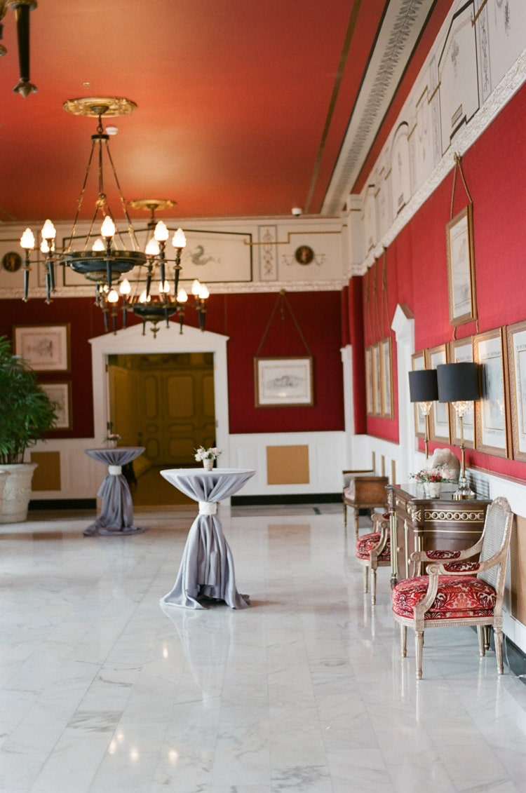 Wedding reception in ballroom with marble flooring, red walls, and natural lighting