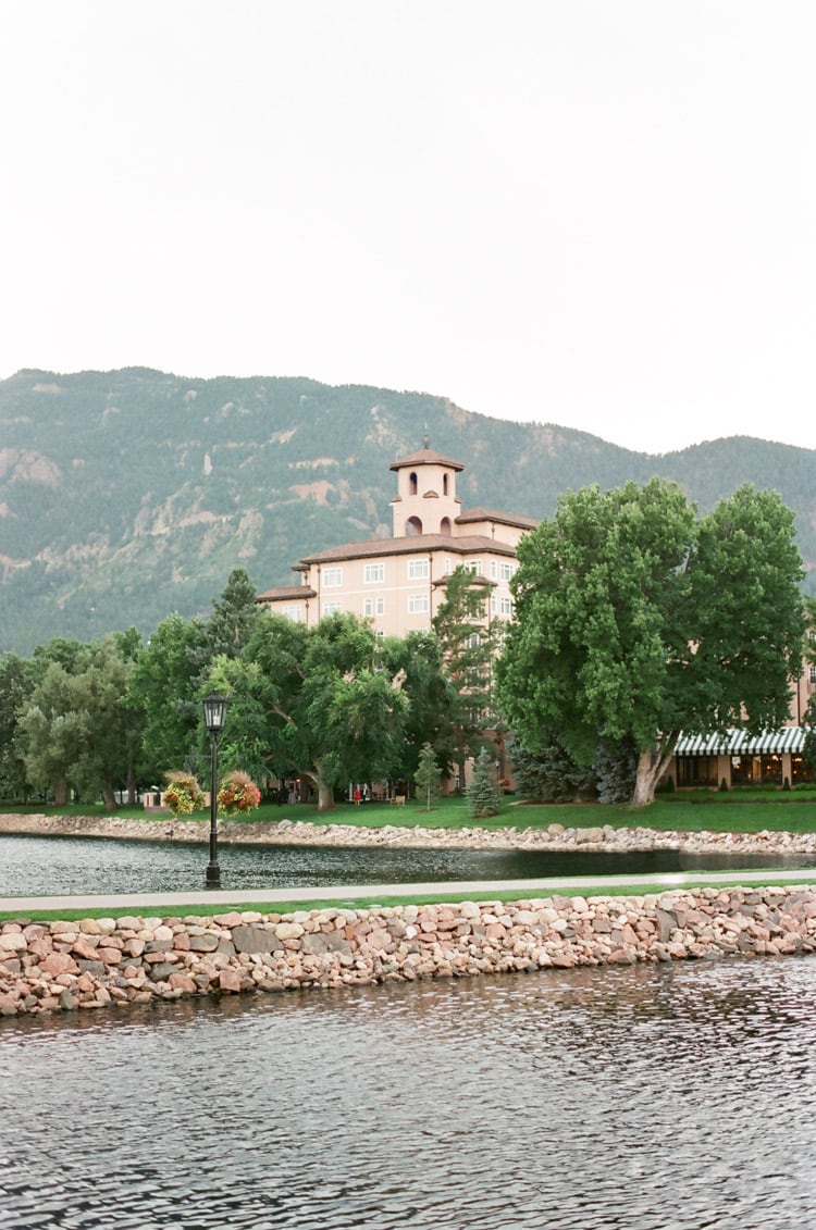 View from the water of Broadmoor resort nestled behind trees and mountain in background