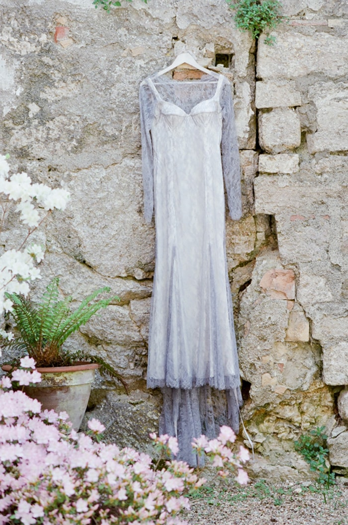 Wedding gown hanging on an old stone wall in Tuscany