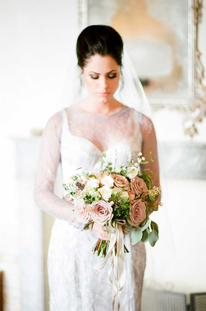 Bride holds a wedding bouquet in a muted color palette