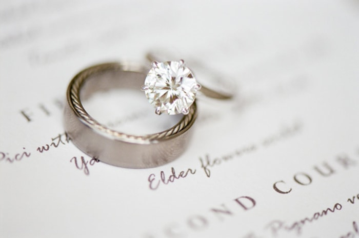 Engagement ring and wedding ring sitting on a wedding invitation