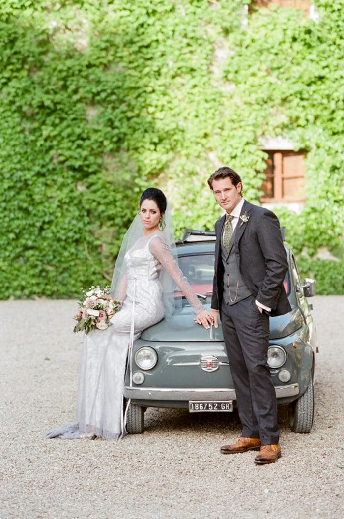 Bride and groom sitting on the hood of an Italian getaway car