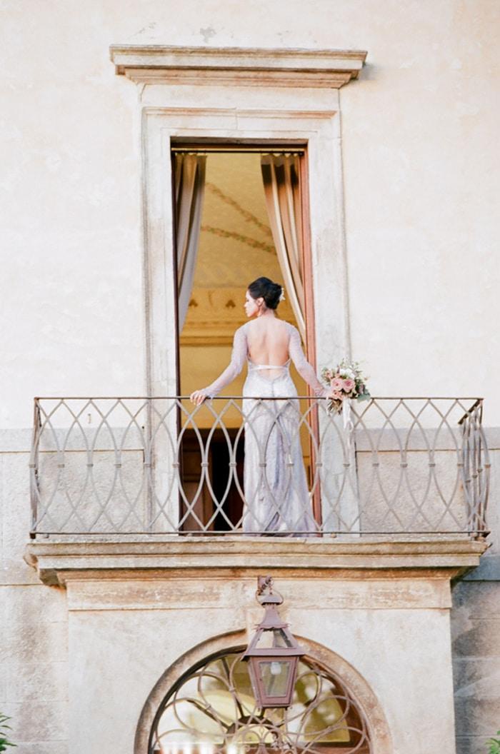 Bride standing on a balcony at Borgo Pignano in Tuscany, Italy