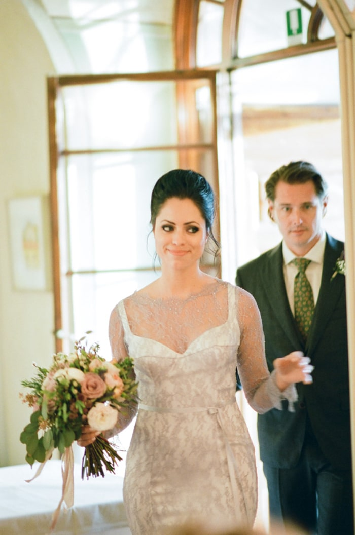 Bride and groom enter their intimate wedding reception at Borgo Pignano in Tuscany