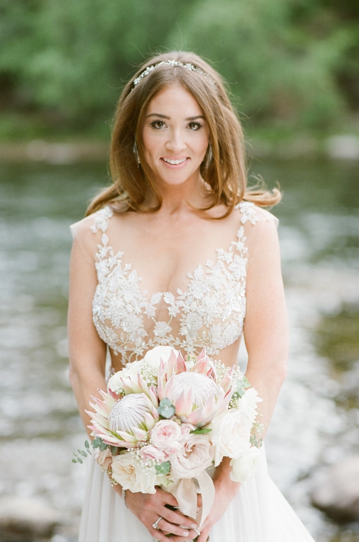 Bride in lace gown holding organic bouquet at her wedding in Beaver Creek Colorado
