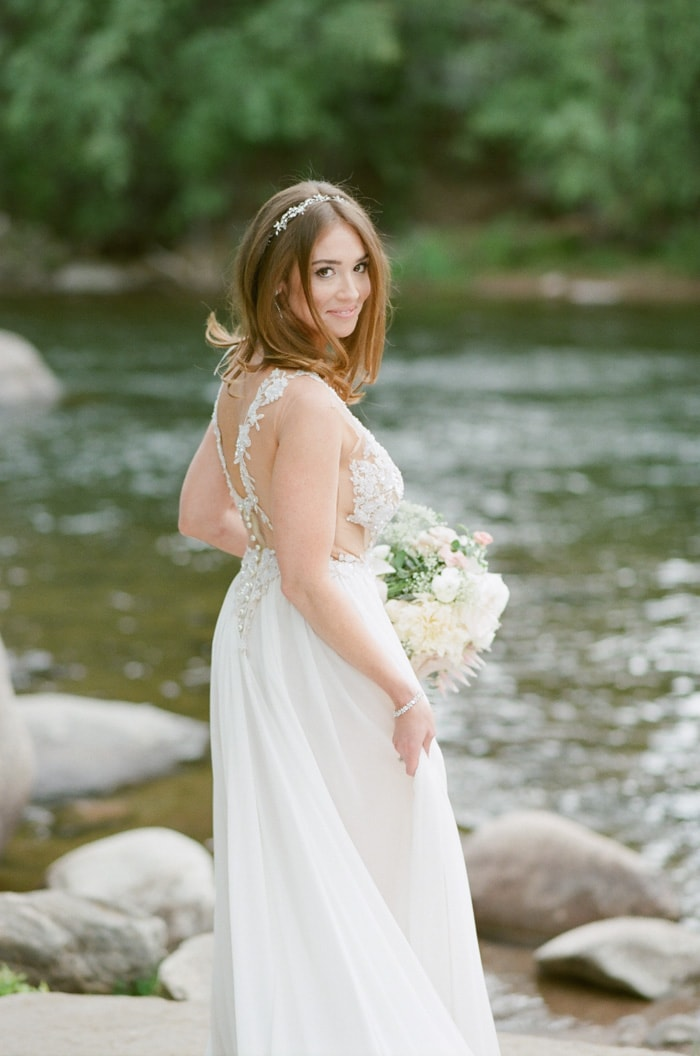 Bride standing in front of a river in Beaver Creek Colorado
