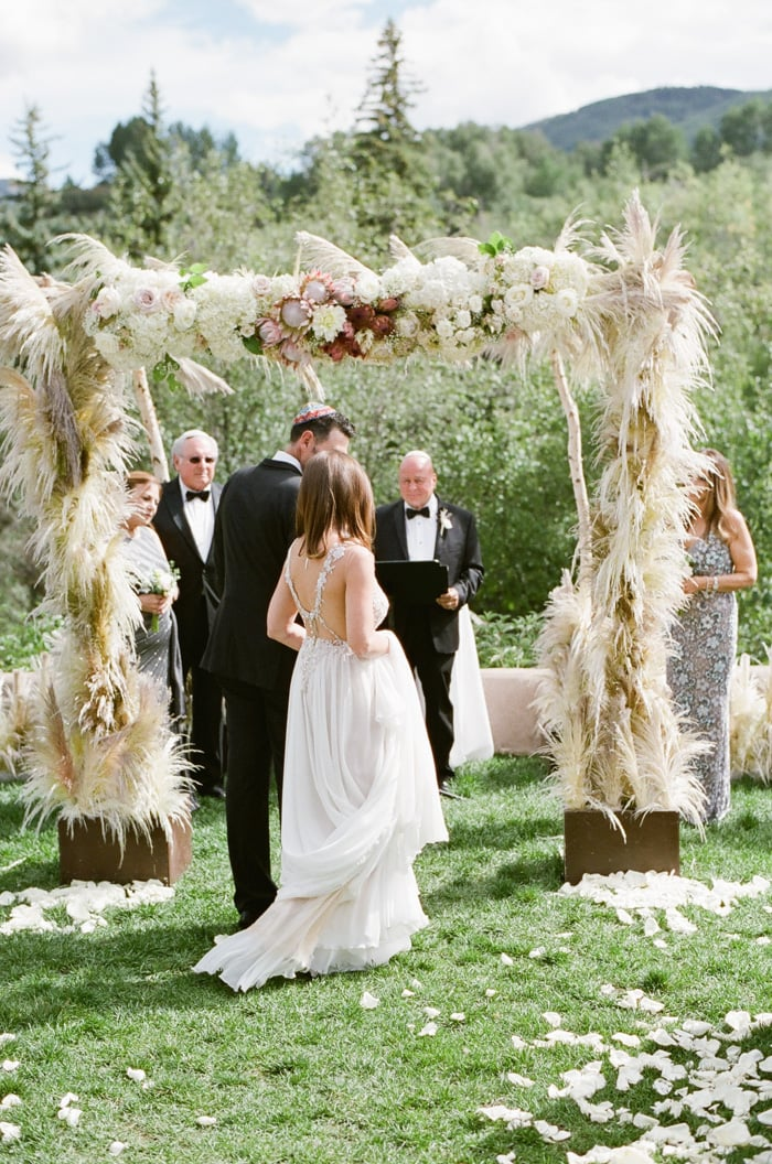 Bride and groom stand in front of a feathergrass chuppah for a Jewish wedding at the Westin Riverfront Resort & Spa in Beaver Creek