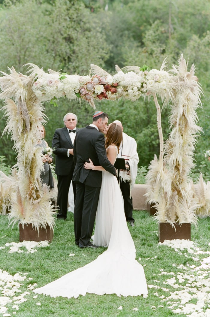 Couple kissing under feathergrass arch at outdoor Colorado wedding in Beaver Creek