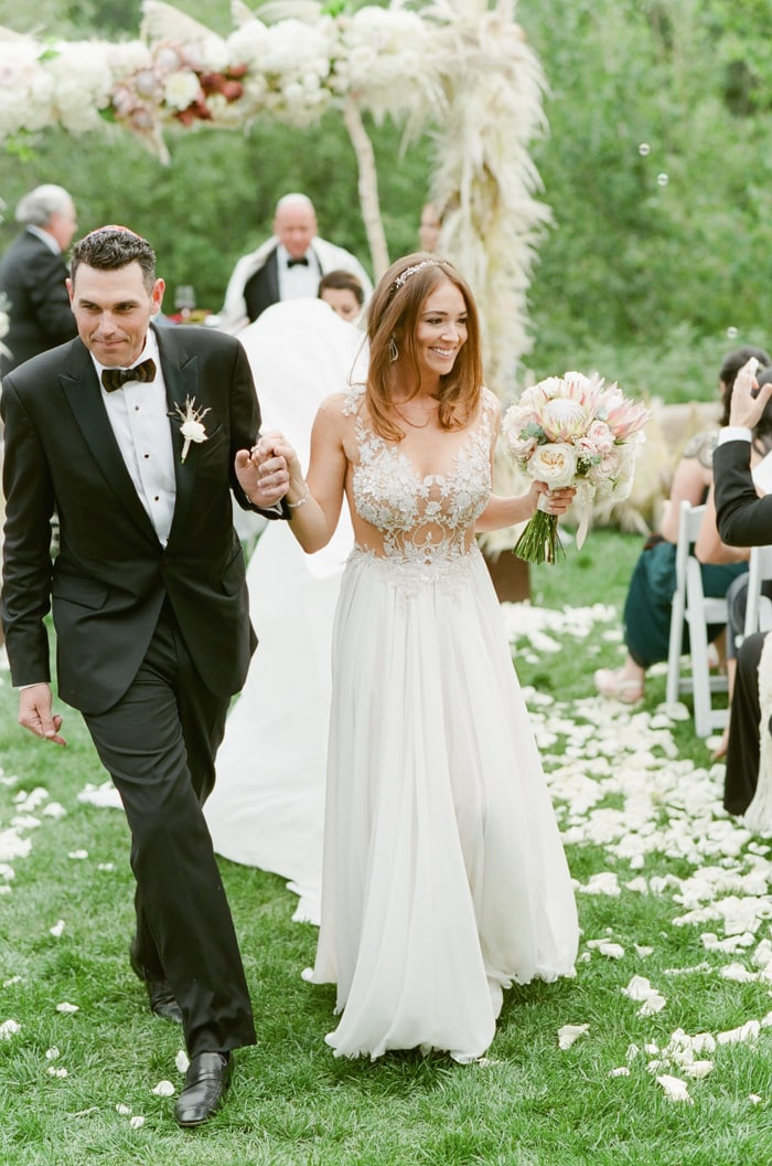 Couple walks down the aisle after their Jewish wedding ceremony in Beaver Creek