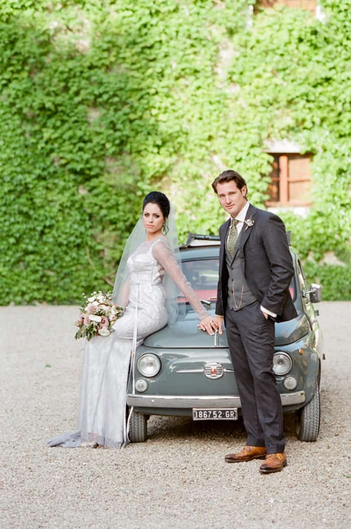 Bride And Groom Leaning On Oldtimer Fiat Cinquecento At Borgo Pignano In Tuscany In Italy With Sposiamovi Events
