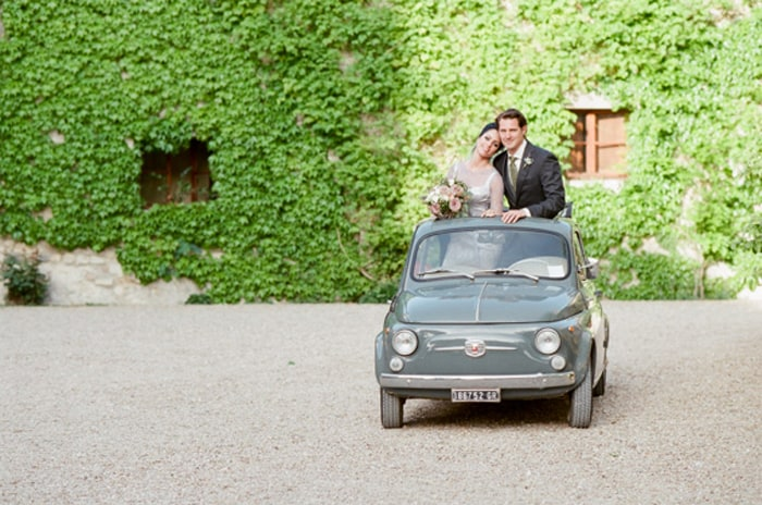 Wedding Couple Standing Inside Oldtimer Fiat Cinquecento At Borgo Pignano In Tuscany In Italy With Sposiamovi Events