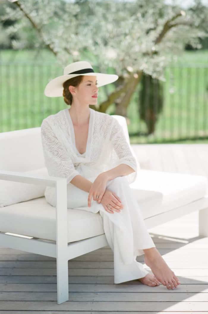 Woman wearing a white lounge suit and wide brim hat by the pool at Domaine De Manville in Provence