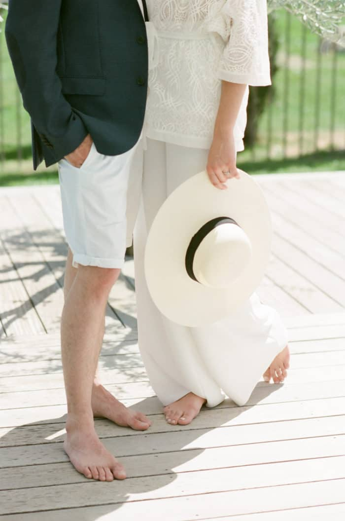 Man and woman standing barefoot next to the pool at Domaine De Manville in Provence
