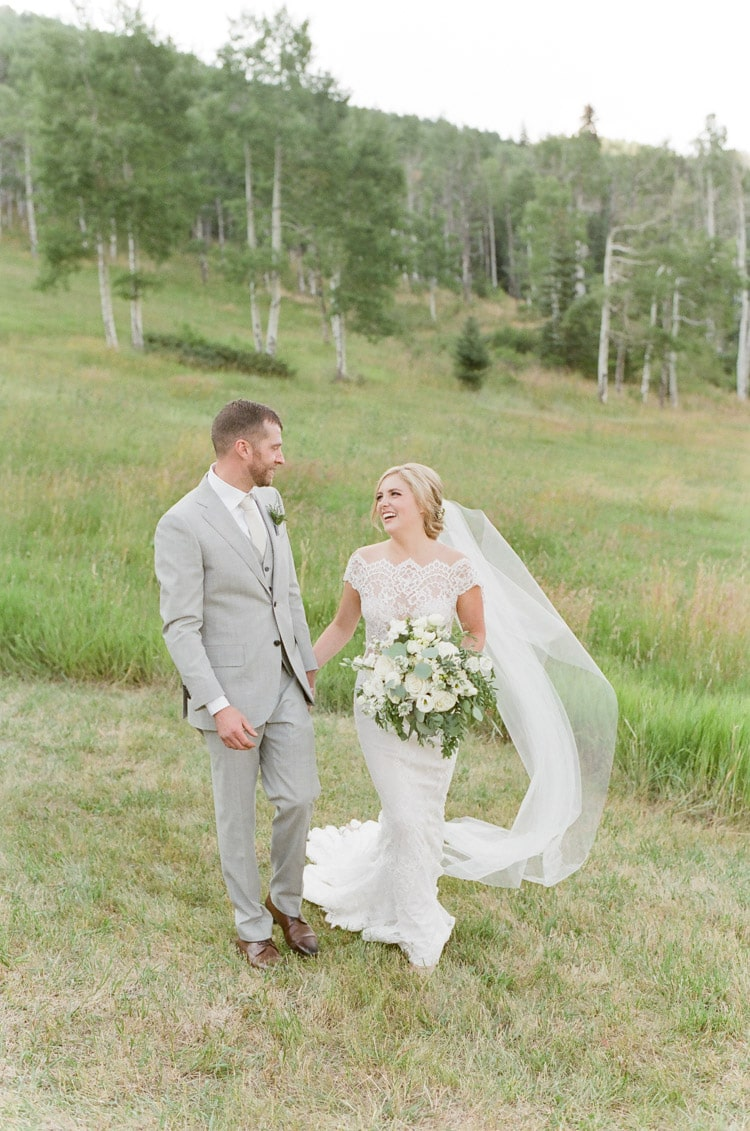 Bride and groom hold hands at their Vail wedding at Eaton Ranch