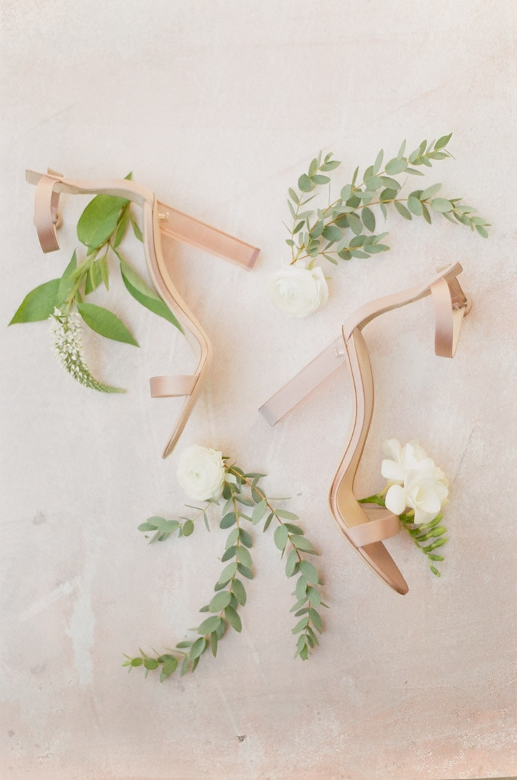 High heels with an ankle strap surrounded by greenery