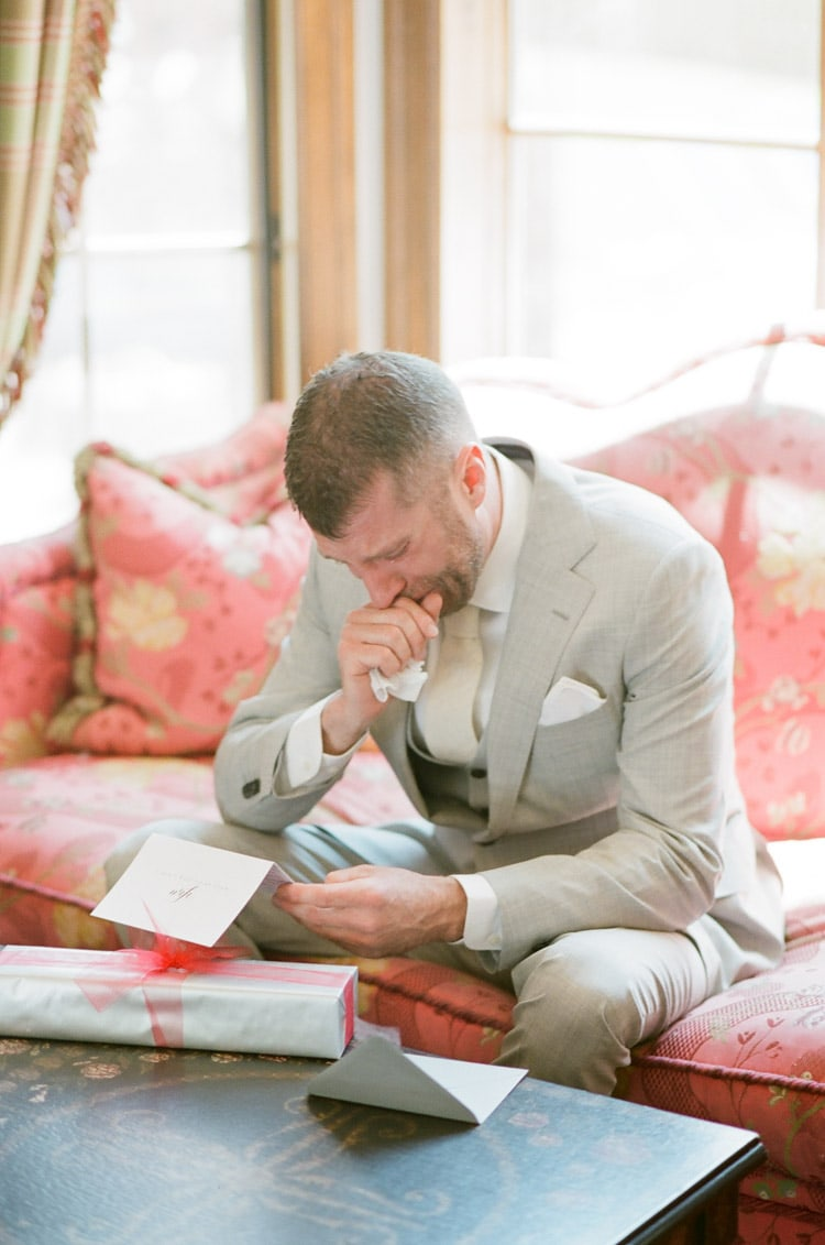 Groom reads a letter from his bride on his wedding day at Eaton Ranch in Vail
