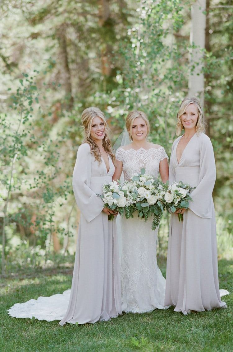 Bride and bridesmaids holding white bouquets at Eaton Ranch wedding in Vail