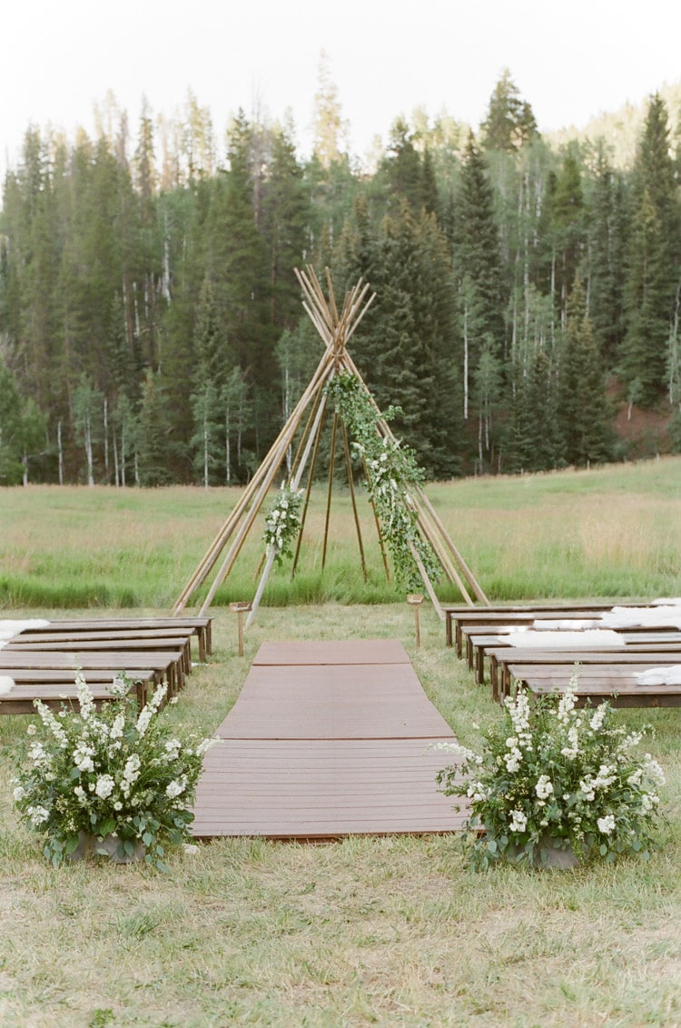 A modern teepee serves as a wedding ceremony backdrop at an outdoor wedding in Vail Colorado at Eaton Ranch