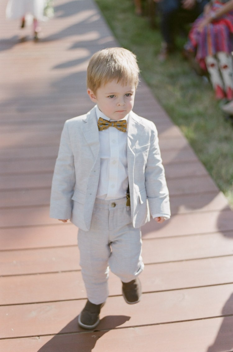 Ring bearer walks down the aisle at an outdoor wedding in Vail Colorado