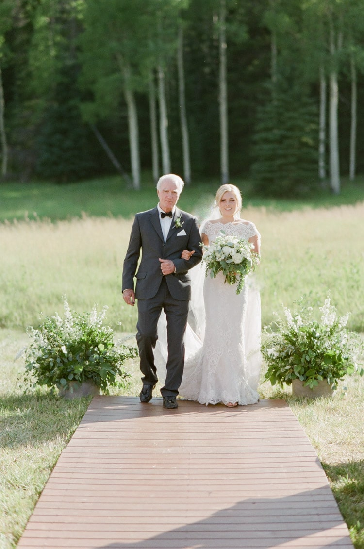 Bride walks down the aisle at an outdoor wedding in Vail Colorado