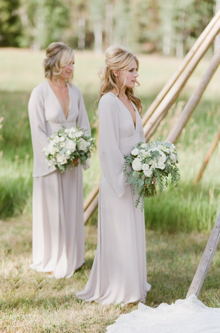 Bridesmaids hold white bouquets at an outdoor wedding ceremony at Eaton Ranch in Vail