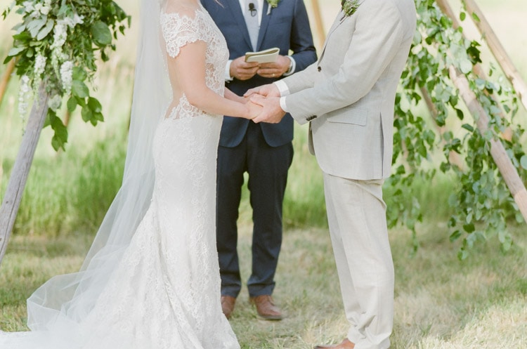 Couple holds hands during their Vail wedding ceremony