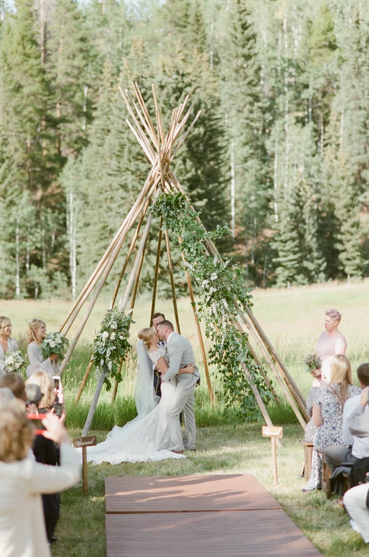 Couple kissing beneath a teepee structure at an outdoor wedding in Vail Colorado at Eaton Ranch