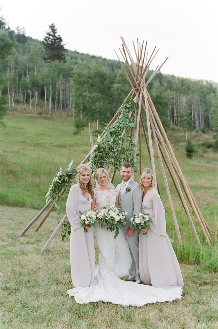 Wedding party standing in front of a teepee frame accented with floral
