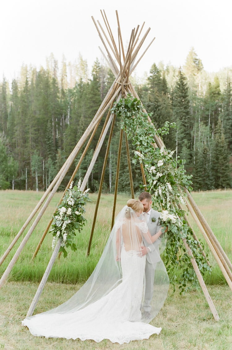 Couple standing in front of a teepee structure at an outdoor wedding in Vail Colorado at Eaton Ranch