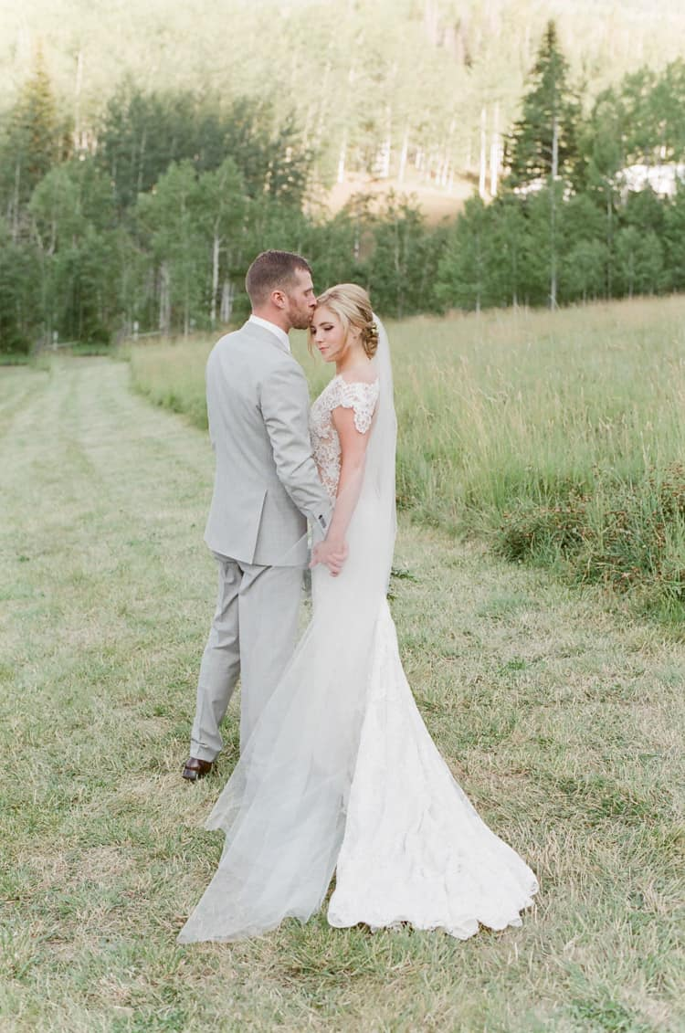 Bride And Groom Kissing In Field At Eaton Ranch Wedding In Vail With Bella Event Design And Planning