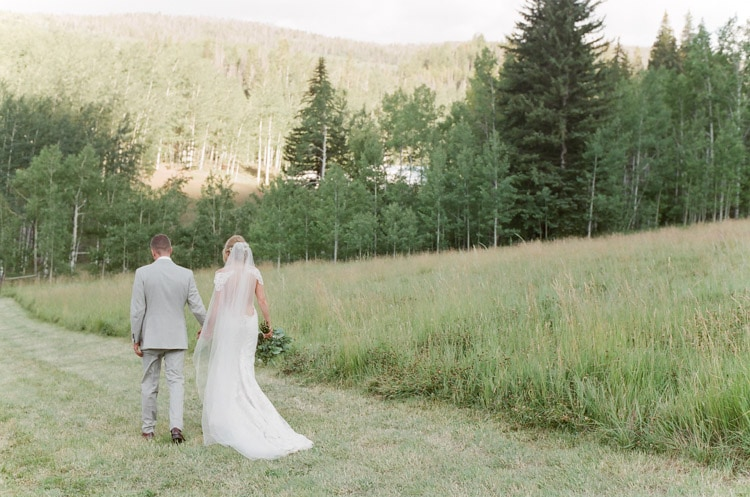 Couple holding hands and walking through a field at Eaton Ranch in Vail