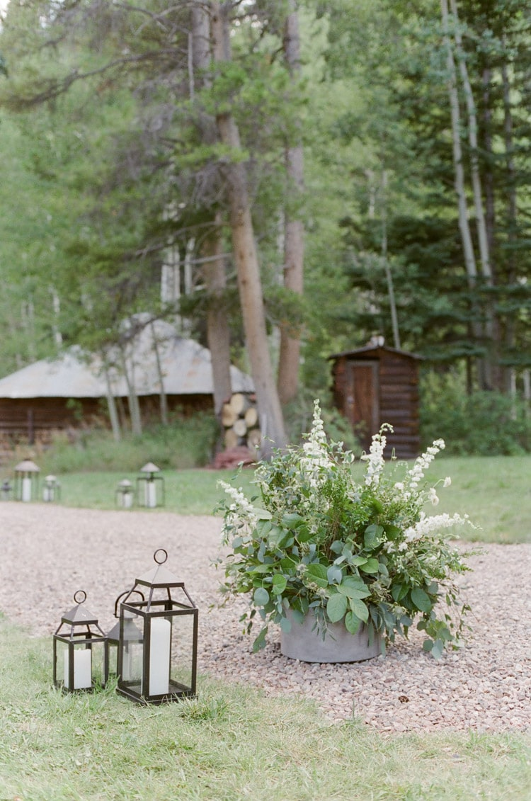 White floral arrangement and two lanterns serve as wedding decor at an outdoor wedding in Vail Colorado