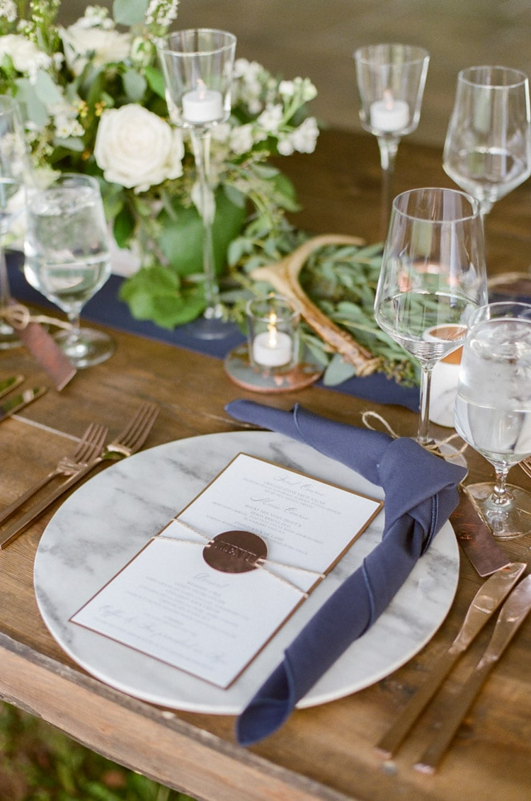 Rustic floral arrangement and place setting at a tented wedding reception in Vail Colorado