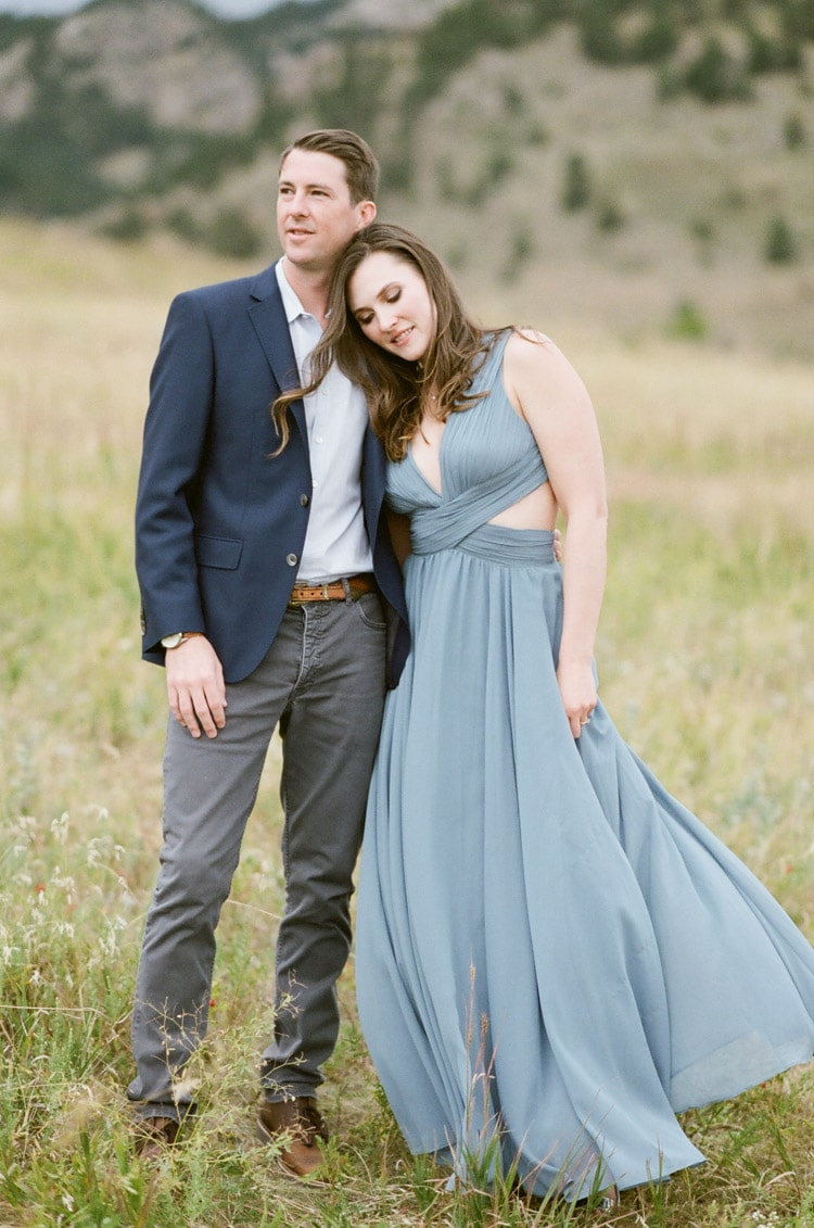 Man and woman pose for engagement portraits at the Flatirons in Boulder Colorado